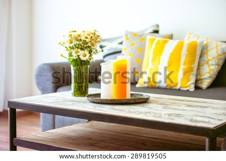 Modern wooden coffee table and cozy sofa with pillows. Living room interior and home decor concept
