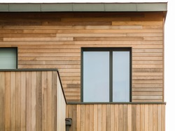 Modern wooden facade with flat roof and aluminium window