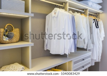 modern wooden wardrobe with clothes hanging on rail in walk in closet design interior #1040083429