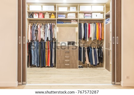 Modern wooden wardrobe with clothes hanging on rail in walk in closet design interior #767573287