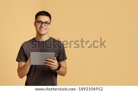 Modern work, social media and online communication. Attractive happy young male student in glasses, with smart watch typing in digital tablet, isolated on beige background, studio shot, free space