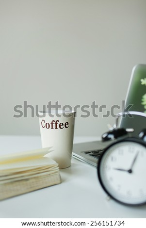 Modern working desk with laptop coffee notepad and alarm clock