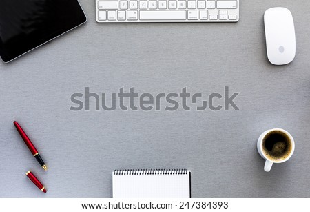 Modern working place on grey wood table. From above view on the well equipped working place surrounded with tablet PC, computer mouse and keyboard, red pen, blank notepad and cup of fresh coffee
