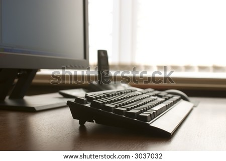 Modern workplace. Computer keyboard, tft monitor and DECT telephone on a wood desk.