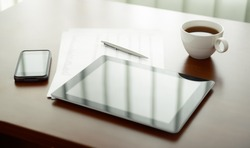 Modern workplace with digital tablet computer and mobile phone, cup of tea, pen and paper with numbers.
