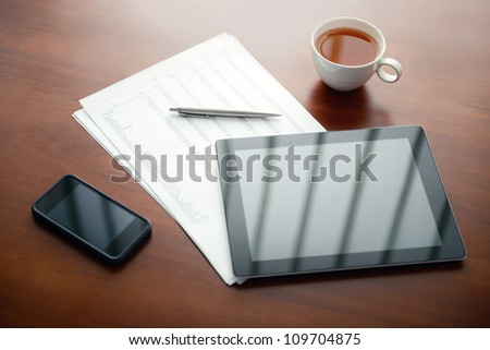 Modern workplace with digital tablet computer and mobile phone, pen and papers with numbers. - stock photo