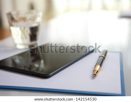 Modern workplace with digital tablet, pen and papers.