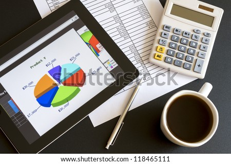 Modern workplace with digital tablet showing charts and diagram on screen, coffee, pen and paper with numbers.