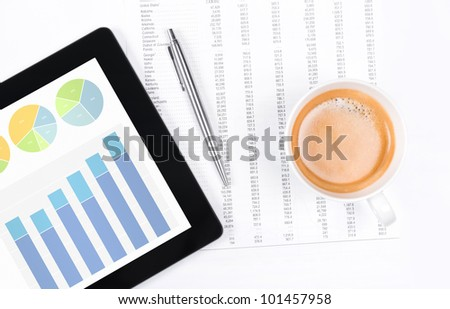 Modern workplace with digital tablet showing charts and diagram on screen, cup of coffee, pen and paper with numbers.