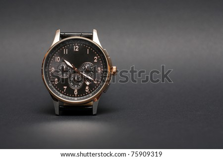 Modern wristwatch standing on nice dark background with copy space