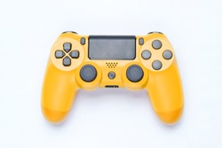 Modern yellow gamepad (joystick) on gray background. Top view