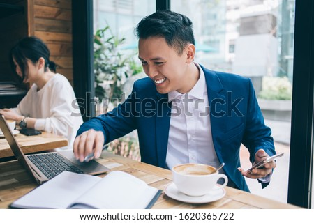 Modern young Asian man in blue suit sitting at wooden table in cafe holding smartphone and working with laptop with wide smile