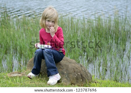 Modern young girl playing computer game in nature