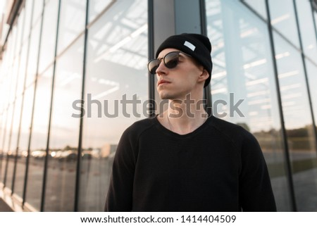 Modern young handsome hipster man in stylish knitted black hat in trendy trendy sunglasses in a t-shirt posing on the background of a glass building in the city. American attractive guy. Street style. #1414404509