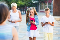 Modern young kids spending time together outdoors using mobile gadgets