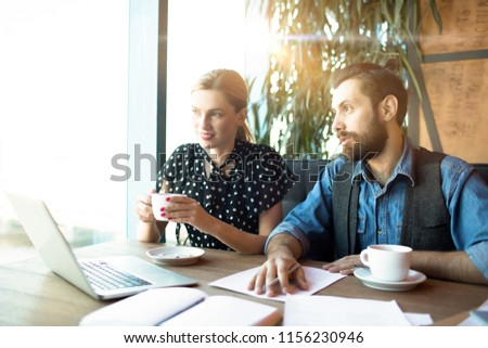 Modern young man and woman sitting with coffee cups at table in cafeteria having papers and laptop for work