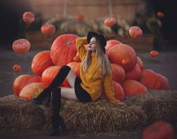 Modern young witch conjures levitating pumpkins. Beautiful girl in a hat near big pumpkins.