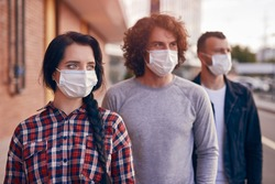 Modern youngster woman and men in casual wear and protective masks standing in row on city street and looking away, while representing coronavirus and new normal lifestyle concept