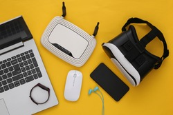 Modern youth gadgets and devices on yellow background. Top view. Flat lay