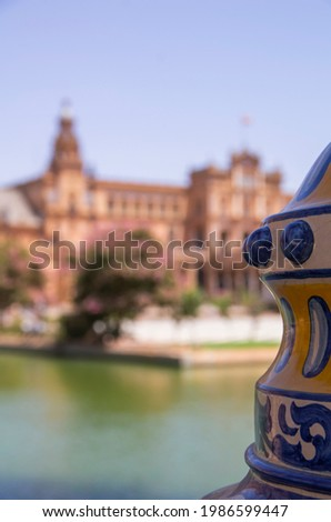 modernist building modernist building in the Plaza de España in Seville, 1929 Ibero-American exposition. A colour full ceramic pot is in the foreground with a blurry backgrround. Regionalist building. Foto stock ©