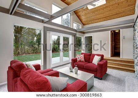Modernized living room with red sofas, and large windows.