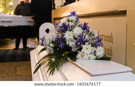 Modest flower arrangement on a white coffin cover next to wall with Bible texts in small Lutheran church, Bouquet from the children of the dead mother. Raasiku, Estonia, Europe. Foto stock ©
