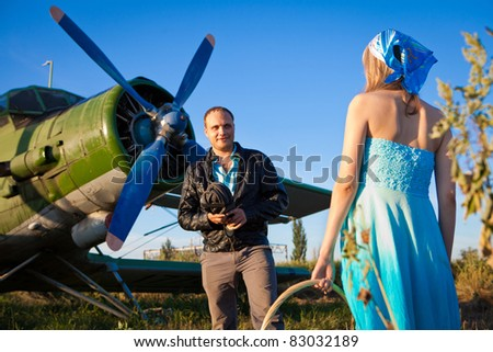 Modest pilot is looking at his girlfriend. Plane on the background
