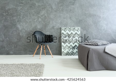 Modest stylish bedroom with bed and chair. Grey walls and wooden floor