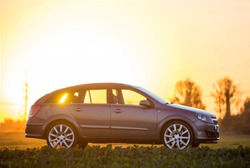 Modified image of a fictional non existent car. Gray car parked in countryside on blurred rural landscape and orange sky at sunset copy space background. Transportation, traveling concept.