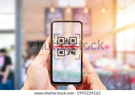 Modified inactive QR Code used. Person scanning QR code with smartphone to register details before enter outlet to comply with contact tracing rule to manage covid-19 spread. Stock photo ©
