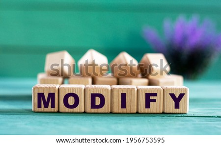 MODIFY - word on wooden cubes on a green background with lavender. Business concept Stock photo ©