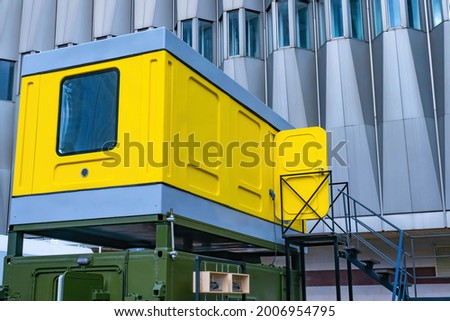 Modular temporary facility. Containerized modular building. Change house or service room module. Yellow two-story shed. Concept - prefabricated modular cabins. Block temporary buildings ストックフォト ©