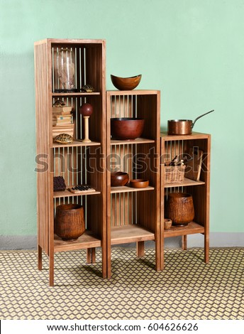 Modular wooden etagere with three descending height units and slatted design displaying an assortment of kitchenware and tools