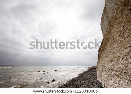 Moens klint majestic chalk cliffs in Denmark on a summer day. Cloudy sky and the sea with small waves.