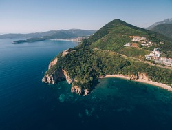 Mogren Beach, near the old town of Budva, in Montenegro. The ancient Mogren Fort on the mountain. Rocky cliffs on the Adriatic coast.