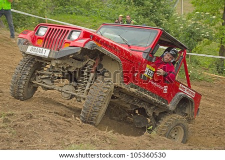 "MOHELNICE, CZECH REPUBLIC - JUNE 10. Unidentified racer at red off-road car leaves steep slope in the ""SHOCK CUP Trial 2012"" on June 10, 2012 in the town of Mohelnice, Czech Republic."