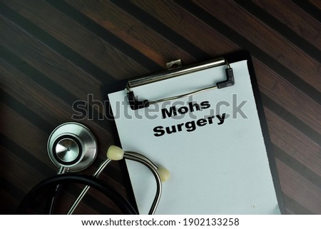 Mohs Surgery write on a paperwork isolated on Wooden Table. Stock fotó ©