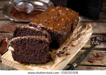 Moist chocolate cake with milk chocolate topping glaze and cocoa powder #558350308