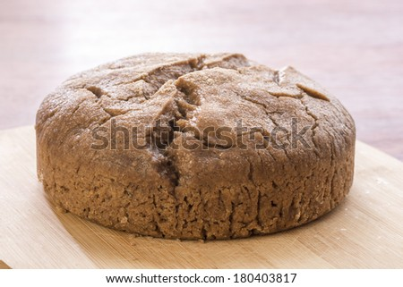 Moist homemade loaf of sourdough bread on cutting board in natural lighting