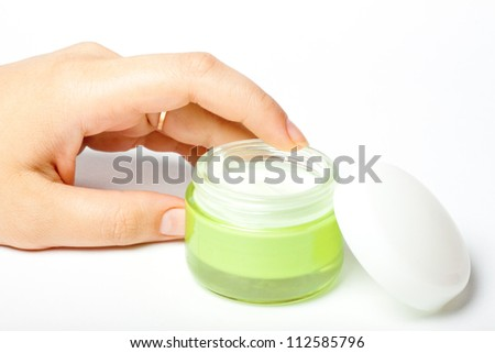 moistening cream in bank and a female hand