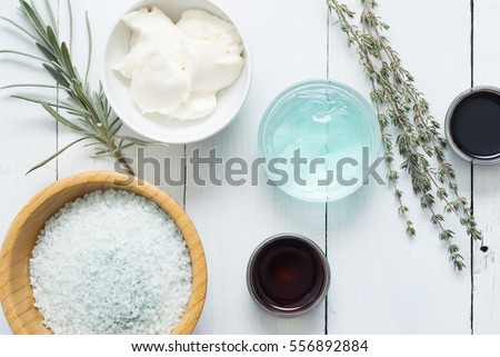 moisturizer, bath salt,  night cream, pumpkin seed oil with lavender and thyme leaves on white wood background #556892884