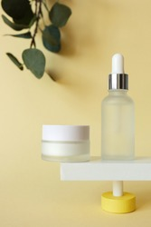 Moisturizer cream and serum in bottle standing on abstract pedestal on pastel yellow background with copy space and defocused eucalyptus leaves, front view. Skincare beauty products mockup, vertical