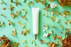Moisturizer cream squeeze cosmetic tube with long nozzle and dried hydrangea flowers on green background. Natural organic cosmetics. Flatlay, mockup