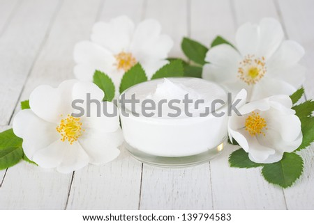 moisturizer cream with field roses on white wooden