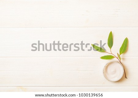 Moisturizer face body skin care wrinkle cream & eucalyptus leaves on white wood textured table background. Retinol moisturizing anti aging antioxidant skincare product for women. Copy space, close up. #1030139656