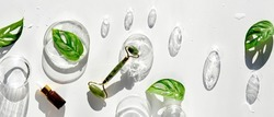 Moisturizer, pink quartz face roller with exotic monstera leaves and orchid flowers and glass baubles. Sunshine, long shadows. Pnoramic flat lay on off white background. Face lymph drainage