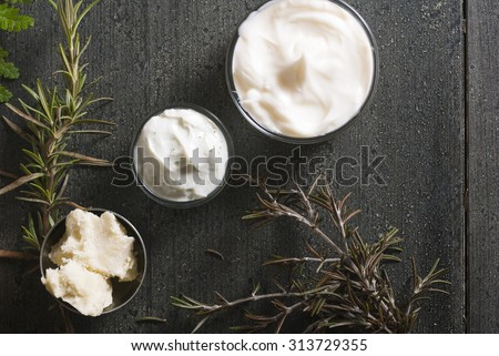 moisturizers and raw shea butter on dark wooden table