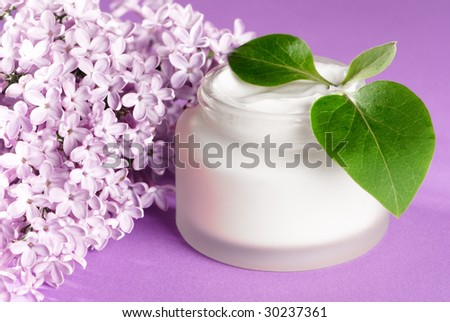 Moisturizing face cream with lilac blossom and leaves on purple background