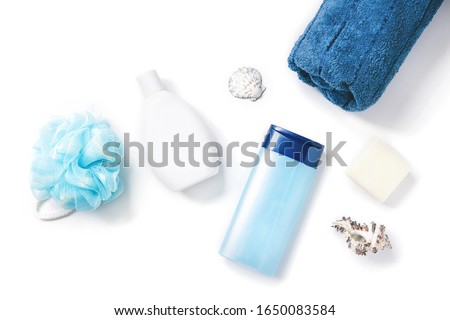 Moisturizing shampoo, shower gel, blue sponge, soap, rolled towel and seashells. Flat lay photo natural spa cosmetics, organic bath products. Toiletries view from above