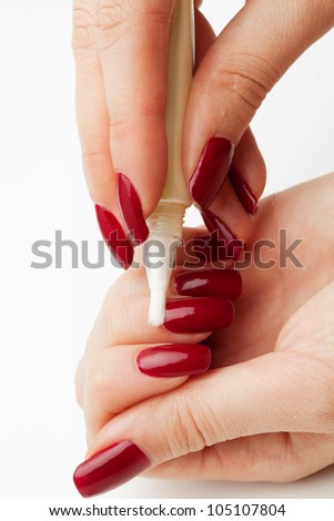 Moisturizing skin around nails (cuticle) in nail service isolated on white